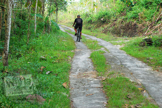 bersepeda di dalam hutan melintasi jalan menanjak bukit di Piyungan, Bantul ke arah watu tompak