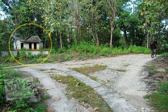 suatu jalan desa pertigaan mistis di tengah hutan dengan makam di lereng perbukitan di kecamatan Piyungan, Bantul