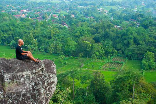 orang berkaos hitam duduk di puncak suatu bukit di kawasan Piyungan, Bantul berfoto dengan latar pemandangan Yogyakarta dari ketinggian