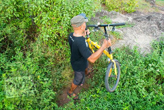 orang berkaos hitam bertopi membawa mengangkat sepeda lipat di kawasan Piyungan, Bantul