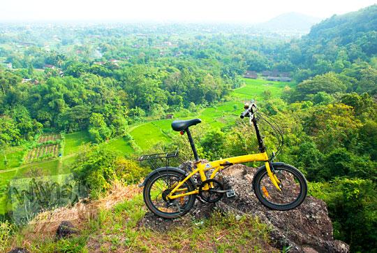 foto sepeda lipat polygon bike 2 work warna kuning di puncak bukit pinggir tebing di Piyungan, Bantul