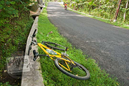 foto sepeda gunung mtb warna kuning tergeletak di jalan turunan di pelosok patuk gunungkidul yogyakarta