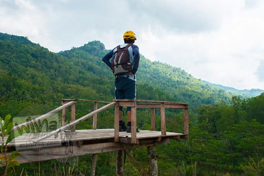 foto pria sedang berdiri pinggir tebing menatap hamparan hutan di gardu pandang objek wisata watu tumpang gedangsari gunungkidul