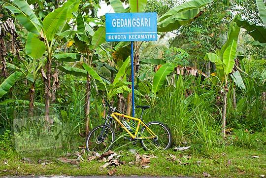 foto sepeda mtb gunung warna kuning di bawah papan batas kota kecamatan gedangsari gunungkidul