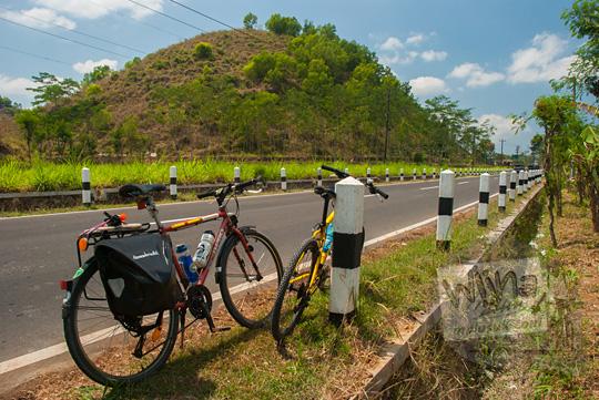 foto sepeda di jalan raya dari kota wonosari arah ke ponjong gunungkidul dengan latar bukit gamping yang indah