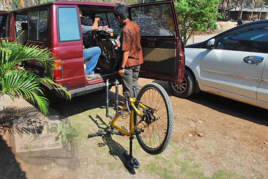 foto sepeda gunung mtb dilepas roda depannya untuk di-loading masuk bagasi mobil kijang
