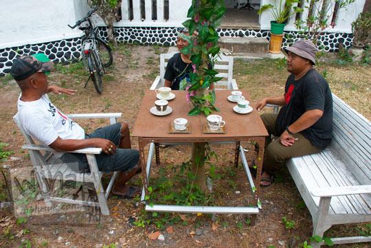 orang duduk di bangku meja taman kebun antik terbuat dari kayu jati dicat putih yang terdapat di halaman depan rumah pocong di banguntapan kotagede yogyakarta