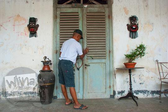 foto ritual khusus yang dilakukan pak nono sang juru rawat pelihara rumah pocong di banguntapan kotagede yogyakarta sebelum membuka pintu utama beliau meminta izin kepada makhluk gaib penunggu rumah dengan cara menempelkan telapak tangan di daun pintu