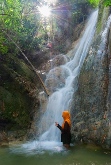 cewek jilbab kuning berpose foto di air terjun curug grojogan pucung seloharjo pundong bantul yogyakarta pada pagi hari
