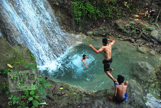 cowok telanjang dada sedang berenang di kedung kolam grojogan pucung seloharjo pundong bantul yogyakarta pada zaman dulu