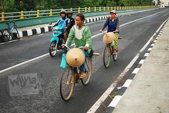 foto ibu-ibu petani sedang bersepeda onthel di jembatan soka kali opak pundong bantul yogyakarta