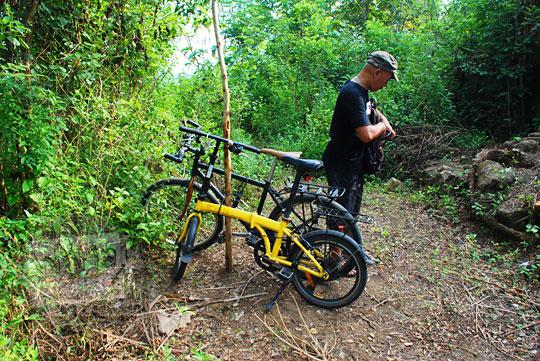 pria berkaos hitam parkir sepeda pohon di tengah hutan desa srimulyo Piyungan Bantul Yogyakarta