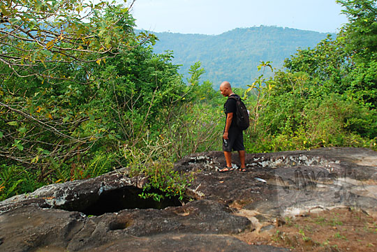 pria gundul plontos botak berkaos hitam melihat lubang di perbukitan srimulyo Piyungan Bantul Yogyakarta lokasi sumur bandung