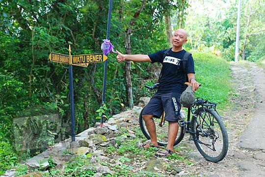 pria berbaju hitam kepala gundul berpose dengan papan petunjuk arah rute ke objek wisata alam watu tumpak atau watu bener di srimulyo piyungan bantul yogyakarta