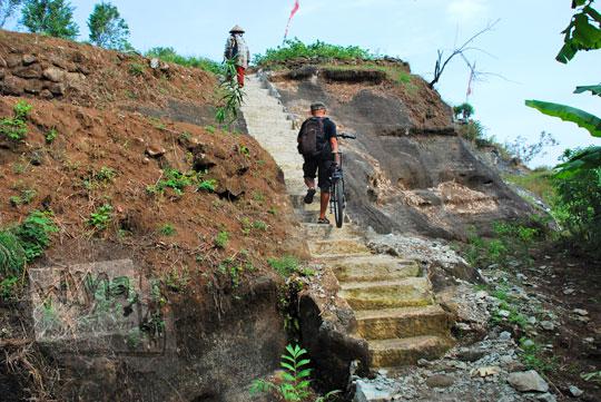 pesepeda mengangkat sepeda menaiki tangga batu tebing ke puncak watu tumpak di piyungan bantul yogyakarta