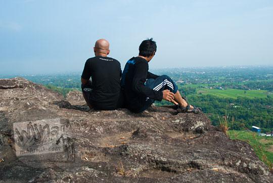 dua pria pakai baju hitam duduk di pinggir tebing obyek wisata alam watu bener di piyungan bantul yogyakarta memandang ke arah langit
