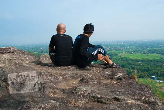 dua pria pakai baju hitam duduk di pinggir tebing objek wisata alam watu bener di piyungan bantul yogyakarta memandang ke arah langit