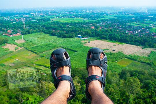 pria pengunjung watu tumpak piyungan bantul yogyakarta berfoto selfie dengan kaki bersepatu sandal latar pemandangan indah pedesaan hijau dari ketinggian