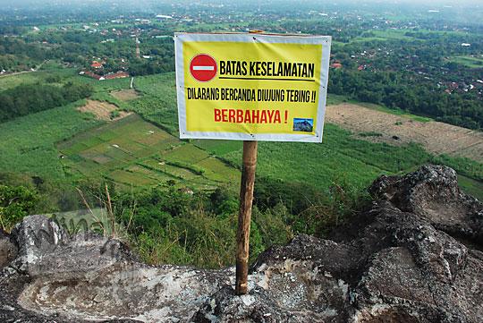 papan larangan bagi pengunjung untuk hati-hati dan tidak bercanda di area keramat obyek wisata watu bener piyungan bantul yogyakarta