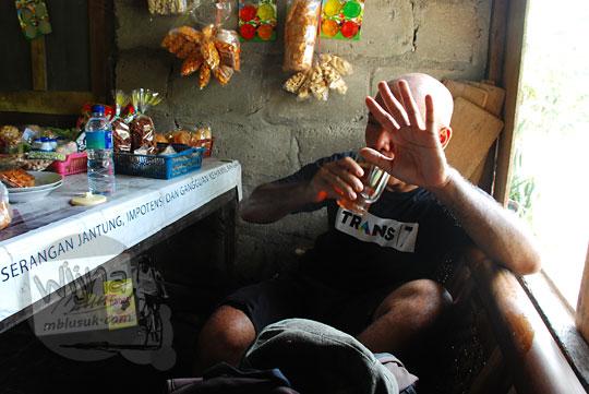 pria berbaju hitam meminum segelas teh di warung tapi menolak tidak mau difoto di desa srimulyo piyungan bantul yogyakarta