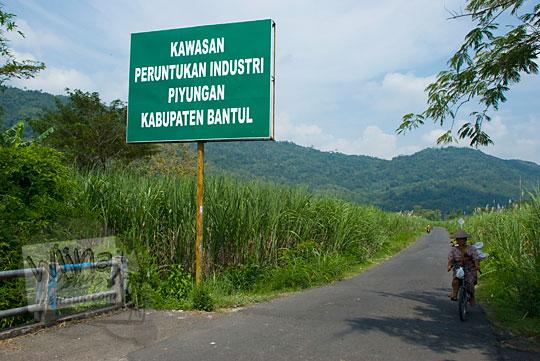 suasana di sekitar lokasi ladang tebu desa srimulyo piyungan terdapat papan kawasan industri dan wanita bersepeda dari sawah