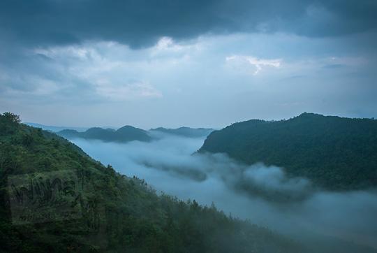 pemandangan lautan kabut pagi hari subuh mendung dari puncak Bukit Panguk Kediwung Mangunan Dlingo Bantul Yogyakarta