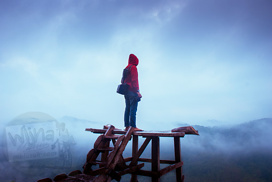 foto cowok pakai jaket merah latar awan langit mendung di Bukit Panguk Kediwung Mangunan Dlingo Bantul Yogyakarta
