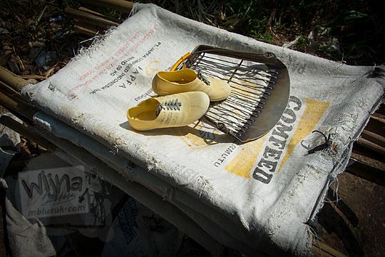 foto ragam jenis macam perlengkapan penambang pasir Kali Progo yaitu wadah pasir dari bekas karung beras, sepatu plastik, dan serokan