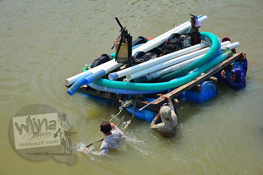 foto bapak-bapak penambang pasir di Kali Progo sedang mendorong rakit yang memuat mesin pompa diesel beserta selang-selang berukuran besar