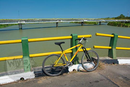 foto sepeda gunung mtb berwarna kuning disenderkan diparkir di jembatan srandakan lama dengan latar langit biru dan jembatan srandakan baru di perbatasan Bantul dan Kulon Progo Yogyakarta