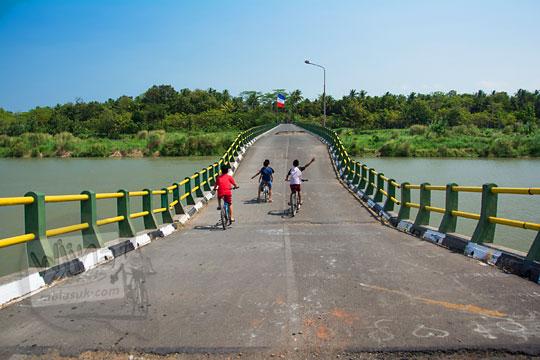 foto tampak belakang anak-anak cowok bersepeda melintasi jembatan srandakan lama ke arah Kulon Progo