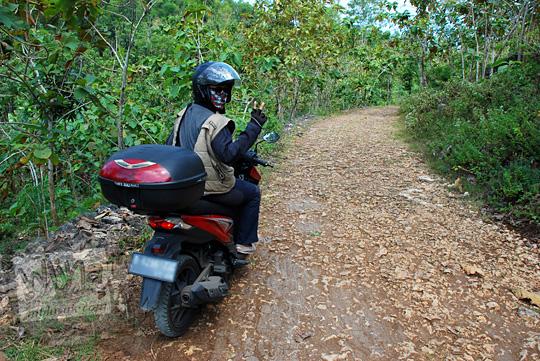 wisatawan cowok pengunjung turis pakai helm jaket naik sepeda motor lewat jalan rusak ke Pantai Timang Gunungkidul Yogyakarta