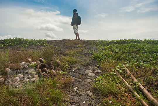 pose cowok dengan jaket berdiri di atas tanggul pemecah ombak pantai glagah kulon progo yogyakarta