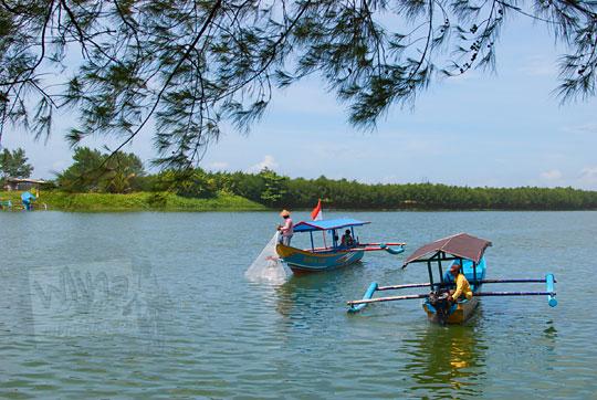 nelayan menjaring ikan dengan dua perahu tradisional di laguna pantai glagah kulon progo yogyakarta