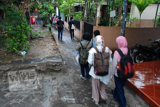 orang-orang jalan kaki menelusuri gang kampung prenggan kotagede