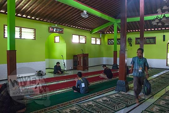wujud pemandangan interior suasana bagian dalam masjid taqorrub kanggotan pleret yogyakarta orang sedang salat berjamaah yang masih disokong oleh tiang-tiang kayu kuno zaman kerajaan mataram islam sultan agung
