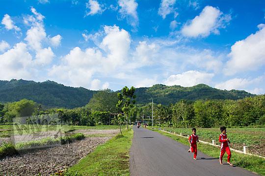 pemandangan dua anak sd berseragam olahraga sedang berlari di jalan aspal dengan latar perbukitan hijau ngliseng muntuk dlingo bantul yogyakarta