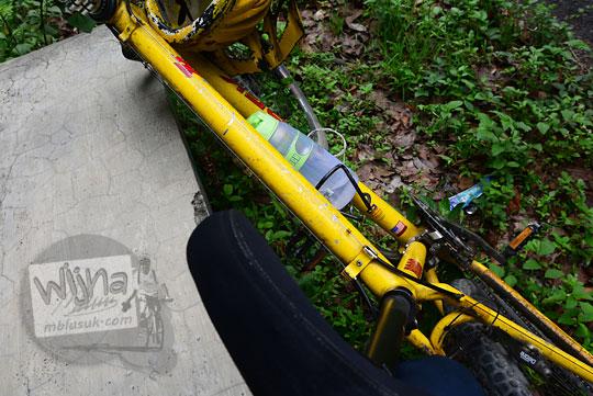 sepeda gunung mtb warna kuning bersandar di buk di pinggir ruas jalan alternatif ke puncak becici dan hutan pinus mangunan