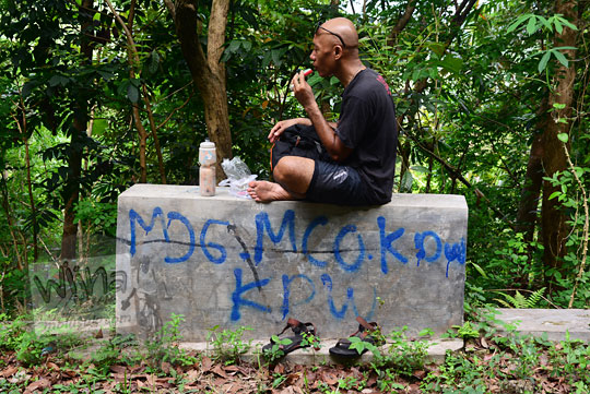 seniman orang jogja bernama bayu indratomo dengan nama lain ki ageng sekarjagad sedang duduk bersila di buk tengah hutan sambil menyantap jajanan pasar pleret
