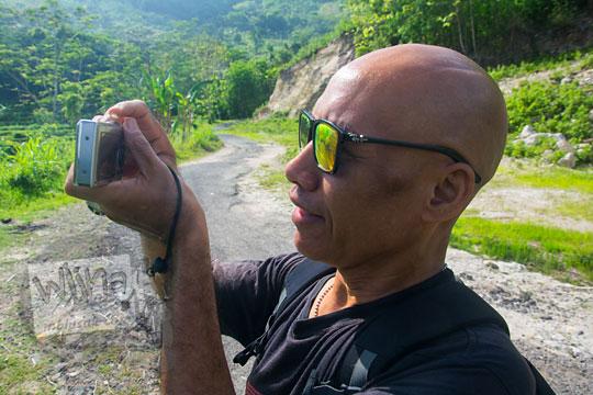 orang jogja berkepala gundul plontos memakai kacamata hitam dan kaos hitam bernama bayu indratomo dengan nama lain ki ageng sekarjagad sedang memotret pemandangan menggunakan kamera digital