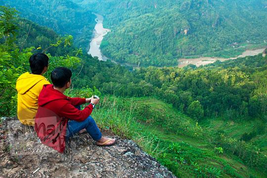 cowok cewek jilbab pacaran pakai jaket kuning dan merah berpelukan di pinggir tebing Jurang Tembelan Kanigoro Mangunan Dlingo Yogyakarta