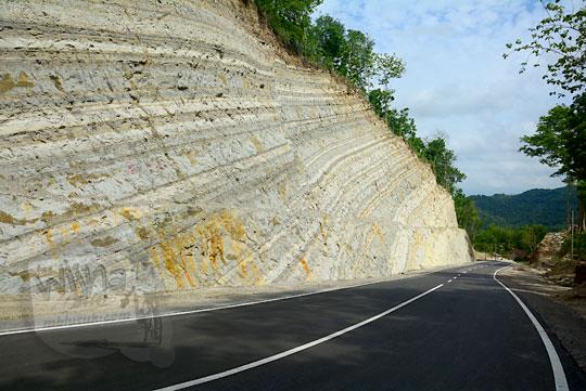 suasana pemandangan jalan raya baru yang dibatasi tebing karst putih tinggi fotogenik instagramable yang mengubungkan desa ngoro-oro patuk gunungkidul dengan jembatan Lemah Abang di gayamharjo prambanan sleman yogyakarta