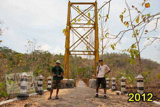 foto dua orang pesepeda berfoto bersama di depan jembatan gantung lemah abang berwarna kuning pada zaman dulu tahun 2012