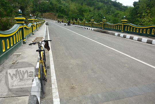 foto sepeda gunung mtb warna kuning bersandar di pinggir jembatan baru Lemah Abang yang masih sepi