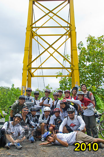 pose para pesepeda yogyakarta dengan helm dan kaos putih berfoto bersama di depan jembatan gantung lemah abang pada zaman dahulu tahun 2010