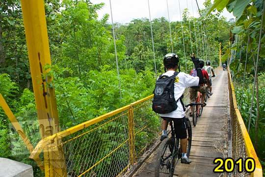 foto pesepeda memakai kaos putih menyeberangi jembatan gantung kuning lemah abang pada zaman dahulu tahun 2010