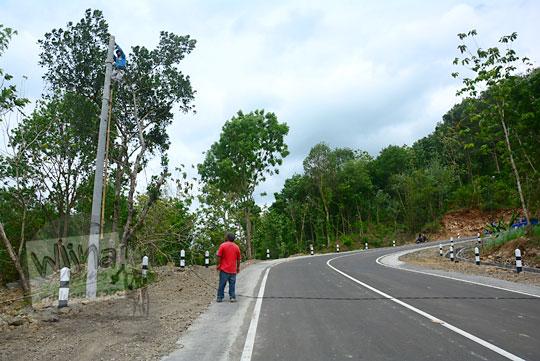 foto para petugas PLN sedang memasang kabel listrik tegangan tinggi di tiang listrik sepanjang jalan baru Lemah Abang Gayamharjo Prambanan Yogyakarta