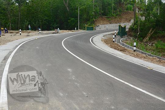 medan jalan raya berupa tanjakan tikungan terjal setelah menyeberangi jembatan Lemah Abang ke arah desa Gayamharjo Prambanan Yogyakarta