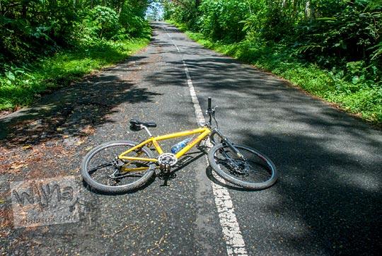 sepeda tergeletak di ruas jalan menanjak di girimulyo, kulon progo