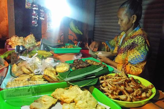 foto wanita tua nenek mbah berkebaya jawa jarit batik rambut disanggul sedang meracik bungkusan nasi kucing di Angkringan Simbah di Jalan Duwet Condong Catur, Depok, Sleman, Yogyakarta
